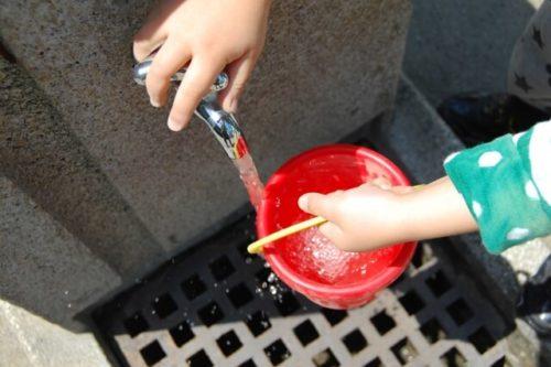 バケツに水を入れる子ども